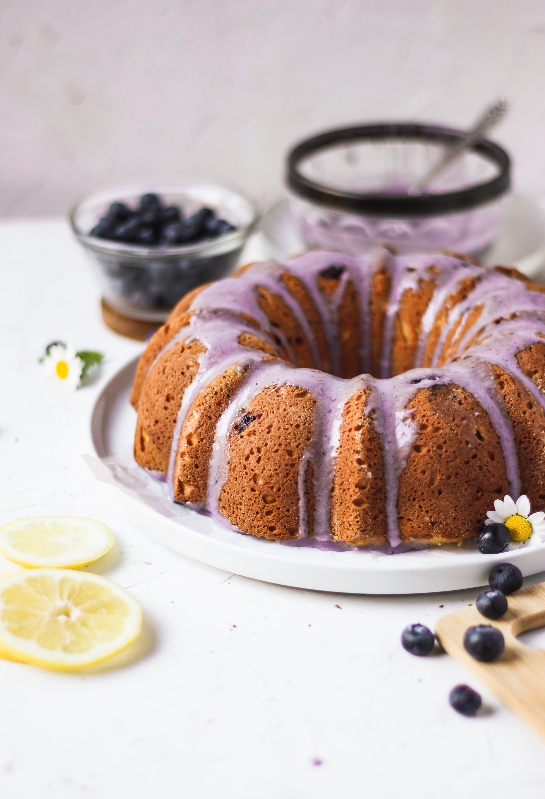 fluffy lemon blueberry bundt cake with purple blueberry glaze